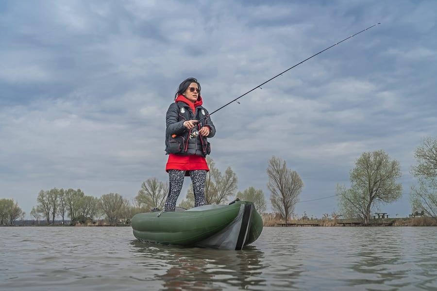Woman fishing on a lake on a stand up fishing kayak