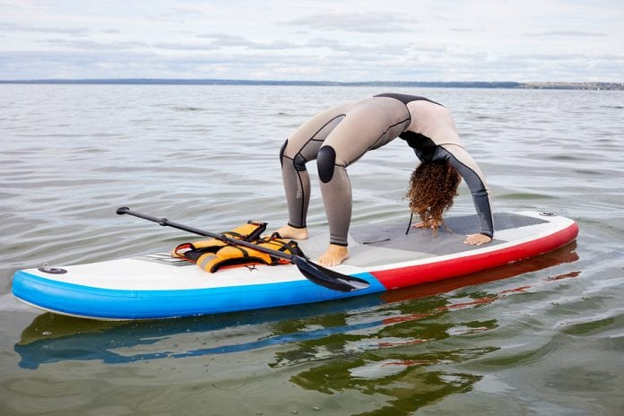 Woman in surfer suit stands in crab position on inflatable SUP